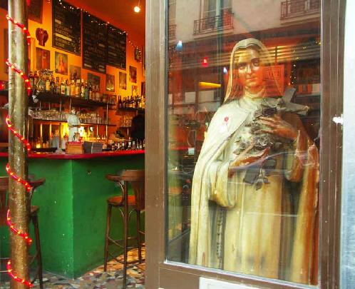 Virgin Bar -- Marais District, Paris -- In the backstreets of the Marais district of Paris there are lots of small bars and bistros.  The Virgin Bar was adorned with many religious icons.  The internet cafe was reflected on Saint Therese who commanded the window of the bar.
